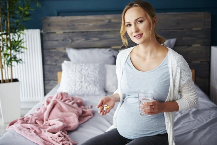 サプリメントを手に持っている妊婦の女性